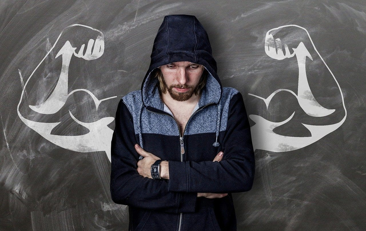 man against chalk board with strong arms on it